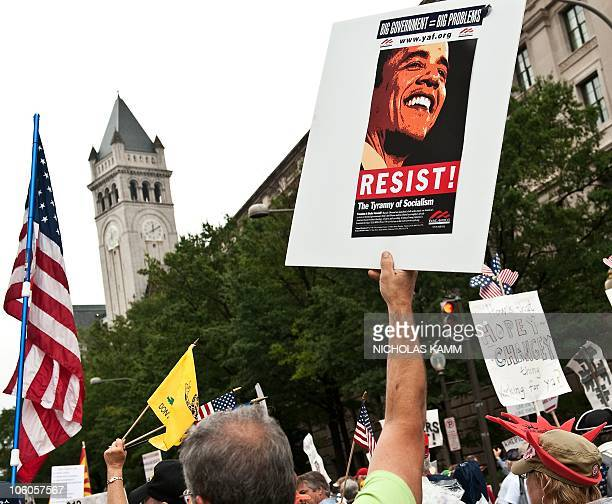 A demonstrator carries a sign calling people to 'resist' US President Barack Obama perceived socialist policies during a march of supporters of the...