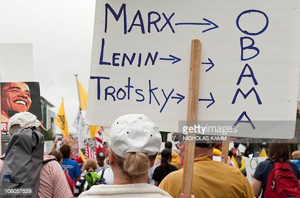 A demonstrator carries a sign equating US President Barack Obama to historical communist politicians Karl Marx Vladimir Lenin and Leon Trotsky during...