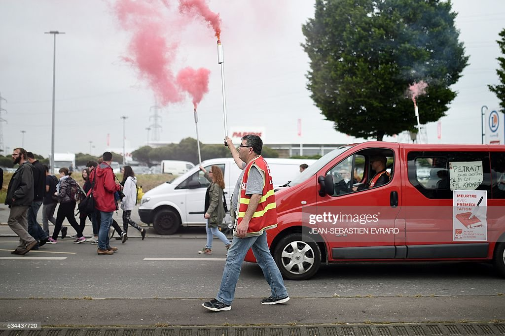 A demonstrator carries a smoking flare on May 26, 2016 in Nantes, western France, during a protest against government planned labour law reforms. The French government's labour market proposals, which are designed to make it easier for companies to hire and fire, have sparked a series of nationwide protests and strikes over the past three months. Masked youths clashed with police and striking workers blockaded refineries and nuclear power stations on May 26 as an escalating wave of industrial action against labour reforms rocked France. / AFP / JEAN