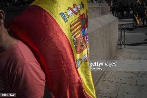 A demonstrator carries a Spanish national flag during a protest for Spanish unity on the Via Laientana in Barcelona Spain on Sunday Oct 8 2017...