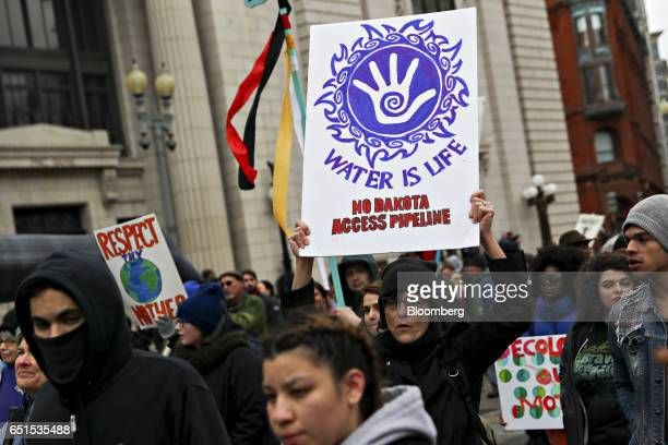 A demonstrator carries a 'Water Is Life' sign during a protest against the Dakota Access Pipeline in Washington DC US on Friday March 10 2017 The...