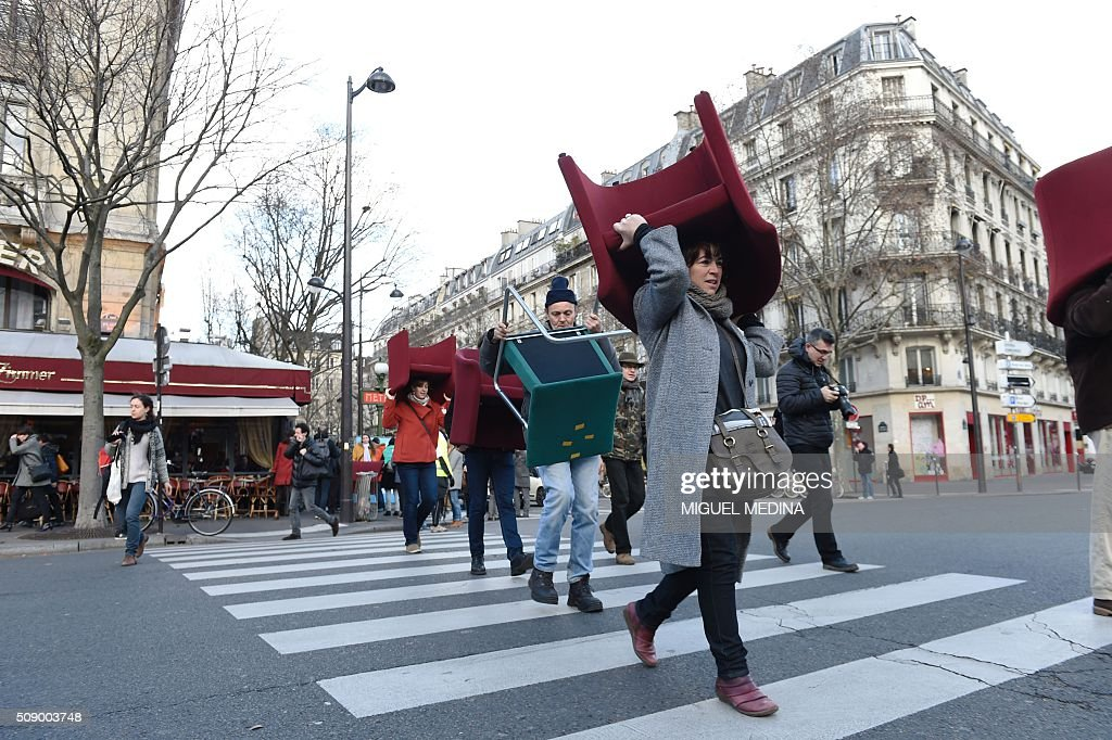 A demonstrator carries on her head a chair taken from bank offices on February 8, 2016 in Paris during a demonstration against bank system and tax fraud, as former French budget minister Jerome Cahuzac goes on trial on February 8 for tax fraud. Cahuzac resigned in disgrace in 2013 after admitting to having a secret Swiss bank account, and faces up to seven years in jail and two million euros ($2.2 million) in fines. AFP PHOTO / MIGUEL MEDINA / AFP / MIGUEL MEDINA