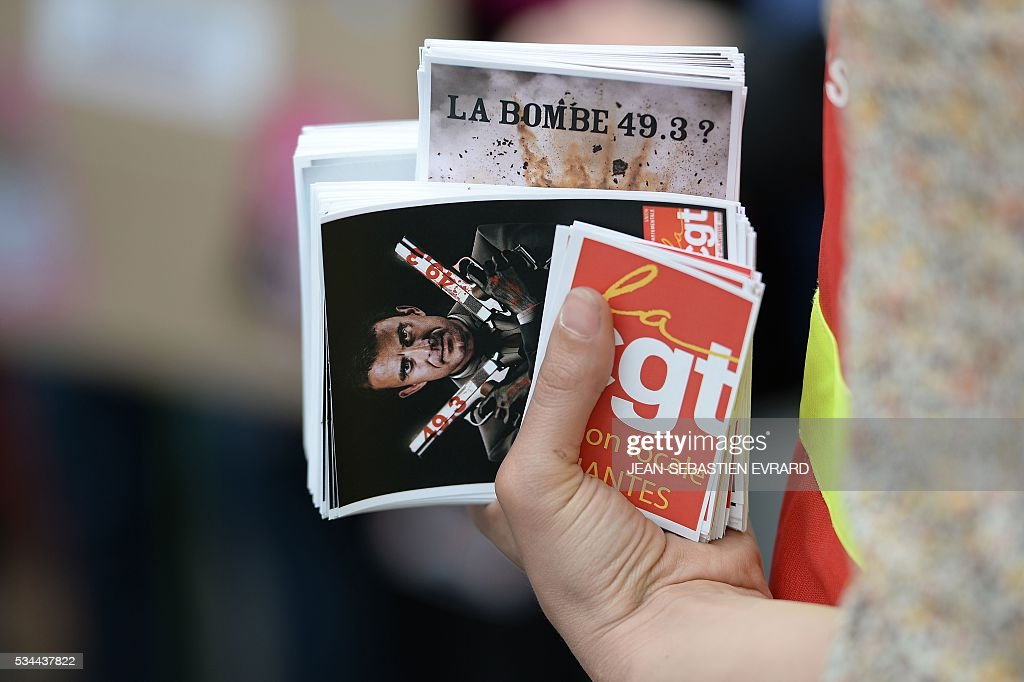 A demonstrator carries stickers on May 26, 2016 in Nantes, western France, during a protest against government planned labour law reforms. The French government's labour market proposals, which are designed to make it easier for companies to hire and fire, have sparked a series of nationwide protests and strikes over the past three months. Masked youths clashed with police and striking workers blockaded refineries and nuclear power stations on May 26 as an escalating wave of industrial action against labour reforms rocked France. / AFP / JEAN