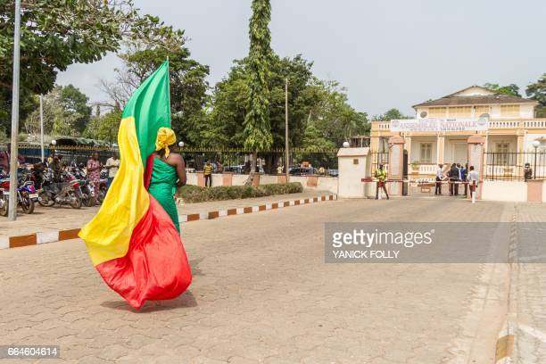 A demonstrator carries the national flag in front of the Beninese National Assembly in Porto Novo on April 4 2017 Beninese National Assembly refused...