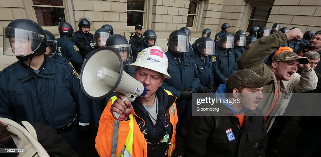 Demonstrator Chad Miller, left front, uses a bullhorn as he stands in front of a line of police officers of during a protest outside the Capitol building in Lansing, Michigan, U.S., on Tuesday, Dec. 11, 2012. Michigan lawmakers approved bills to prohibit mandatory union dues in workplaces as thousands of chanting protesters thronged the Capitol. Photographer: Jeff Kowalsky/Bloomberg via Getty Images