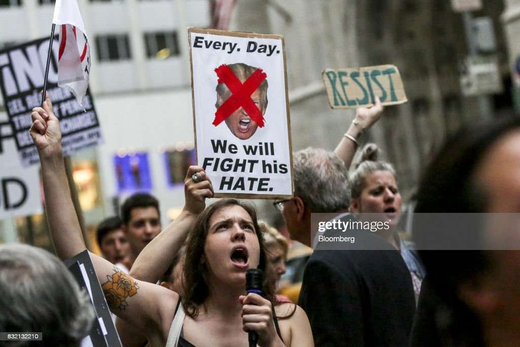 A demonstrator chants and holds a sign during the 'Defend DACA & TPS' rally outside of Trump Tower in New York, U.S., on Tuesday, Aug. 15, 2017. A day after belatedly faulting white supremacists for deadly clashes in Virginia, President Donald Trump returned to his controversial position that there was 'blame on both sides' for the weekend violence, saying that liberal counter-protesters also bore responsibility. Photographer: Jeenah Moon/Bloomberg via Getty Images