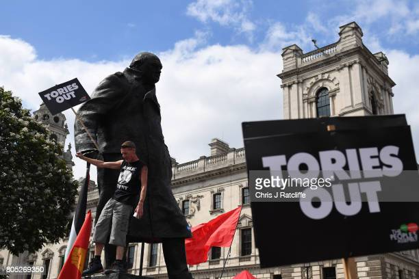 A demonstrator climbs the Statue of Winston Churchill as he waits for Labour Party leader Jeremy Corbyn to speak during the 'Not One Day More' march...