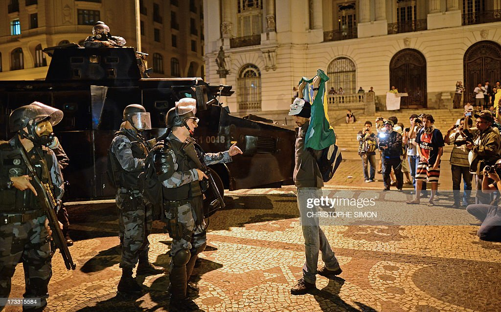 A demonstrator confronts riot police officers in Rio de Janeiro on July 11, 2013 after clashes erupted in parts of the city following a march by Brazilian workers in a day of industrial action called by major unions to press demands for better work conditions. Demonstrators on Thursday blocked roads and staged protest rallies across the country on the 'National Day of Struggles' which was called by the country's five leading labour federations during last month's mass street protests to demand better public services and an end to endemic corruption.