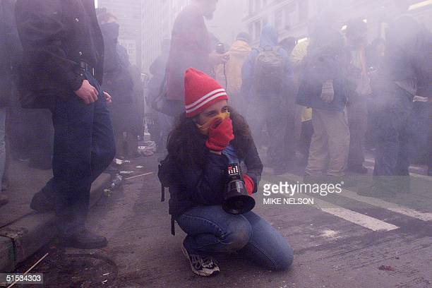 A demonstrator covers her mouth with a scarf to protect herself from tear gas following street clashes with riot police in downtown Seattle...