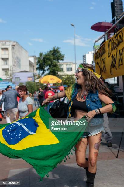 A demonstrator dances with a Brazilian flag during a protest against Brazilian President Michel Temer and government corruption at Largo da Batata in...