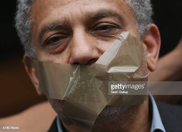 A demonstrator demanding freedom for AlJazeera reporter Ahmed Mansour stands with his mouth tapes shut to symbolize the persecution of journalists in...