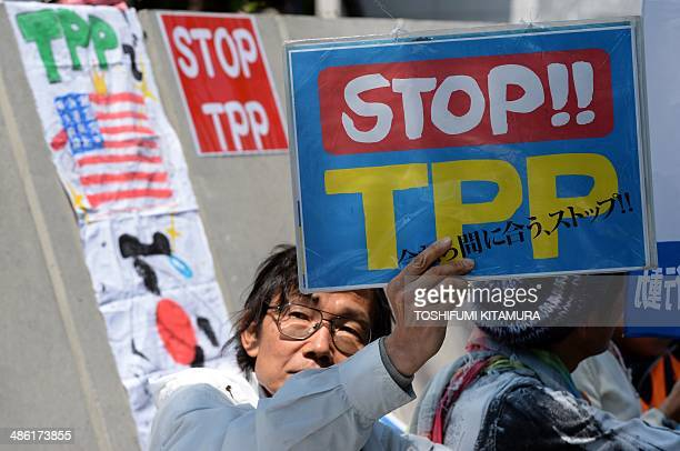 A demonstrator displays a placard to protest against the Trans Pacific Partnership trade deal at a sitin demonstration in front of the parliament...
