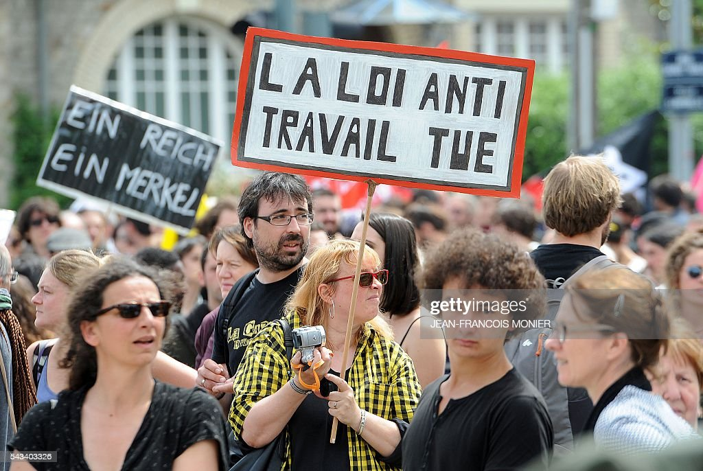 A demonstrator displays a placard which translates as 'The 'Anti' labour law kills' during a protest against controversial labour reforms on June 28, 2016 in Rennes. / AFP / JEAN