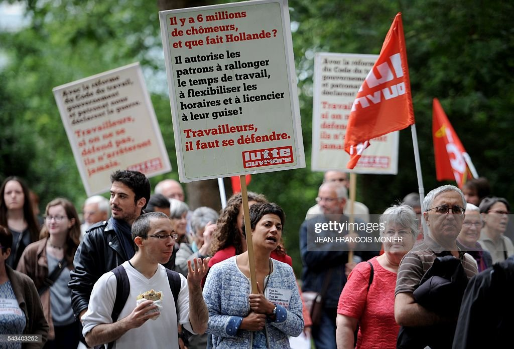 A demonstrator displays a placard which translates as ' There are Six million unemployed and what does Hollande do? He allows employers to lengthen working hours, arrange schedules to suit themselves and fire people at will. Workers must defend themselves' during a protest against controversial labour reforms on June 28, 2016 in Rennes. / AFP / JEAN