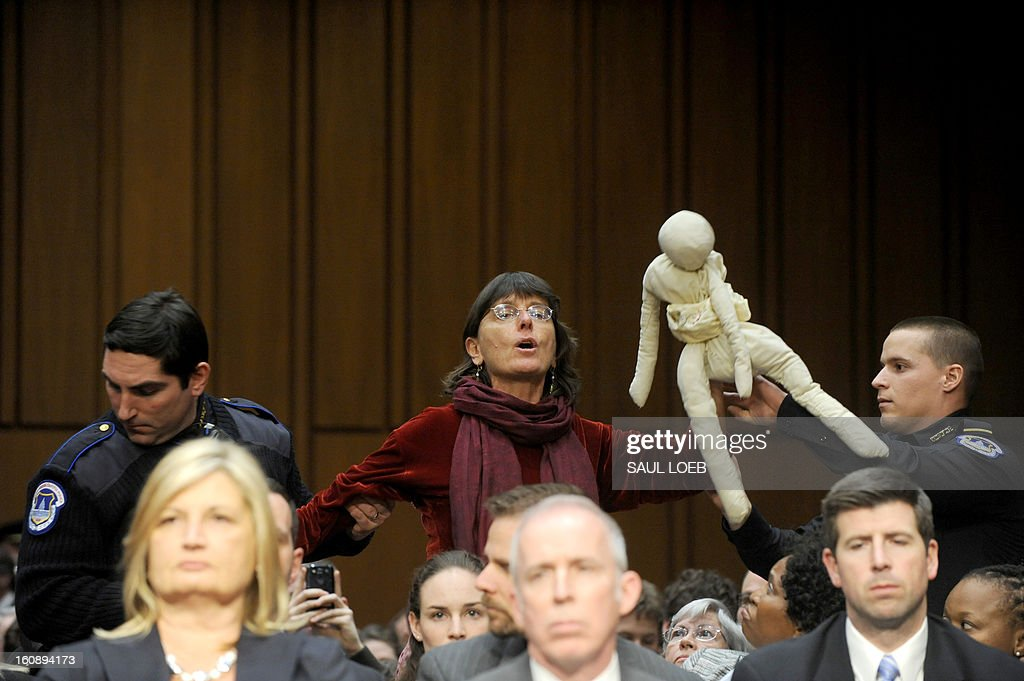A Demonstrator disrupts the confirmation hearing of John Brennan, US President Barack Obama's nominee to be director of the Central Intelligence Agency (CIA), before the Senate Intelligence Committee on Capitol Hill in Washington, DC, on February 7, 2013. The hard-nosed architect of the US drone war against Al-Qaeda, John Brennan, will on Thursday face difficult questions about secret assassinations from senators weighing his nomination to lead the CIA. Committee chair, Sen. Diane Feinstein, D-CA, cleared the room after several outburts by protesters. AFP PHOTO / Saul LOEB