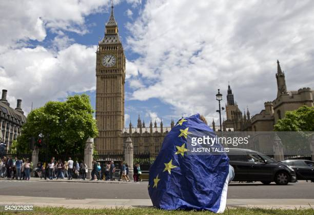 A demonstrator draped in an EU flag sits on floor during a protest against the outcome of the UK's June 23 referendum on the European Union in...