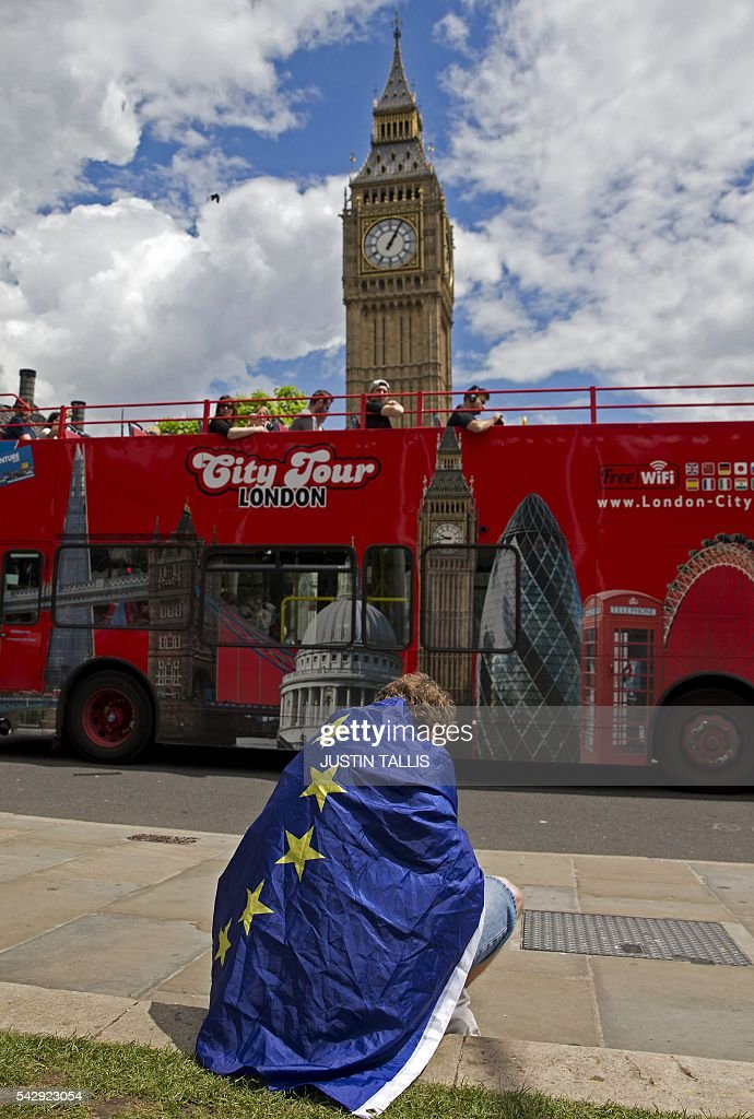 A demonstrator draped in an EU flag sits on floor during a protest against the outcome of the UK's June 23 referendum on the European Union (EU), in central London on June 25, 2016. The result of Britain's June 23 referendum vote to leave the European Union (EU) has pitted parents against children, cities against rural areas, north against south and university graduates against those with fewer qualifications. London, Scotland and Northern Ireland voted to remain in the EU but Wales and large swathes of England, particularly former industrial hubs in the north with many disaffected workers, backed a Brexit. / AFP / JUSTIN