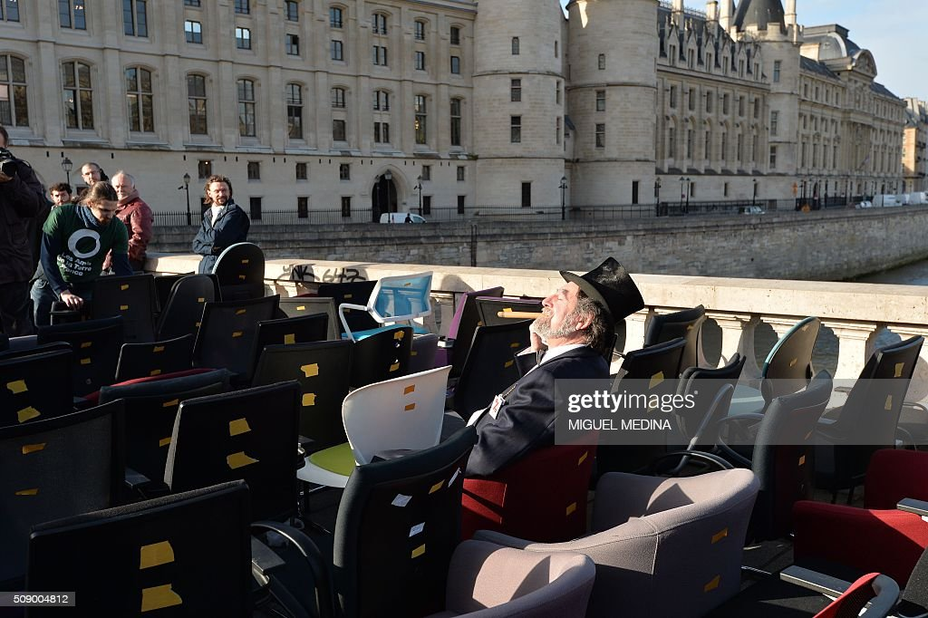 A demonstrator dressed as a banker caricature poses among chairs taken from bank offices on February 8, 2016 on the pont au change near the Court of Paris during a demonstration against bank system and tax fraud, as former French budget minister Jerome Cahuzac goes on trial on February 8 for tax fraud. Cahuzac resigned in disgrace in 2013 after admitting to having a secret Swiss bank account, and faces up to seven years in jail and two million euros ($2.2 million) in fines. AFP PHOTO / MIGUEL MEDINA / AFP / MIGUEL MEDINA