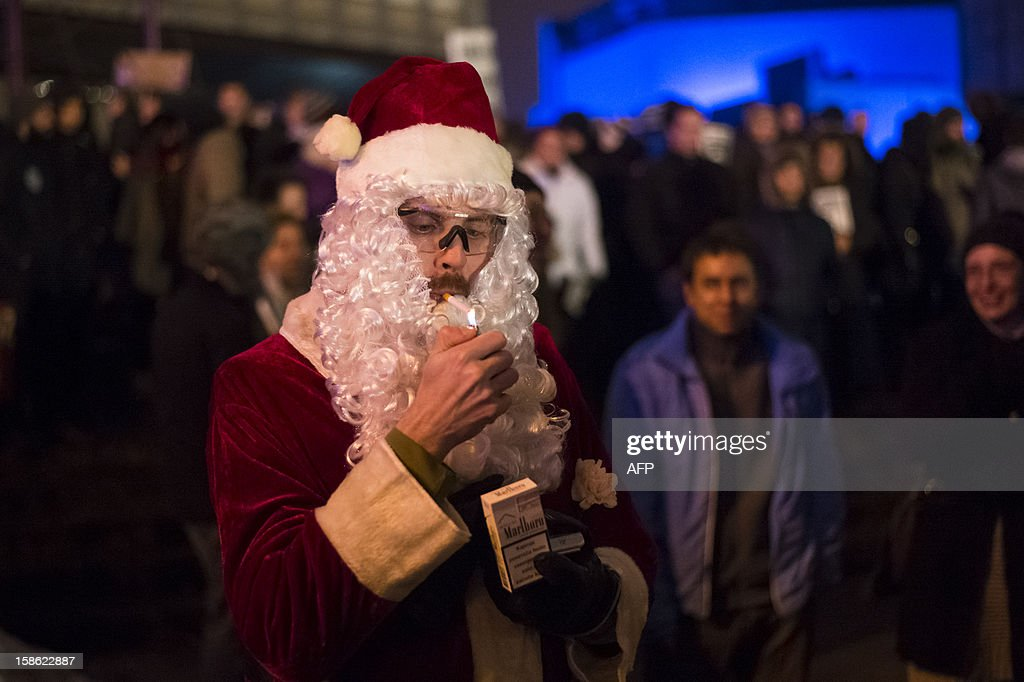 A demonstrator dressed as a Santa Claus lights his cigarette during an antigovernment protest in Ljubljana on December 21, 2012. Slovenia has been rocked by protests in recent weeks amid public anger over corruption and painful austerity cuts that are aimed at preventing the small eurozone country needing a bailout.