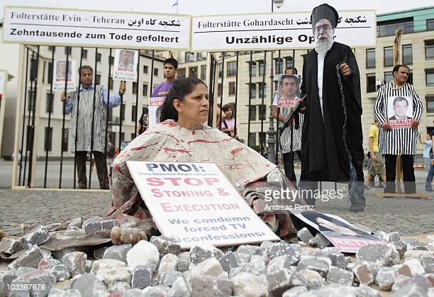 A demonstrator dressed as a victim of a stoning execution and a man dressed as Iranian Supreme Leader Ayatollah Ali Khamenei join Iranian exiles...
