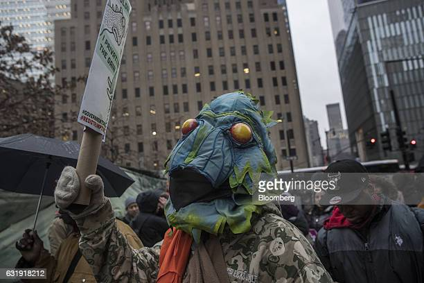 A demonstrator dressed like a swamp creator holds a sign during a protest outside Goldman Sachs Group Inc headquarters in New York US on Tuesday Jan...