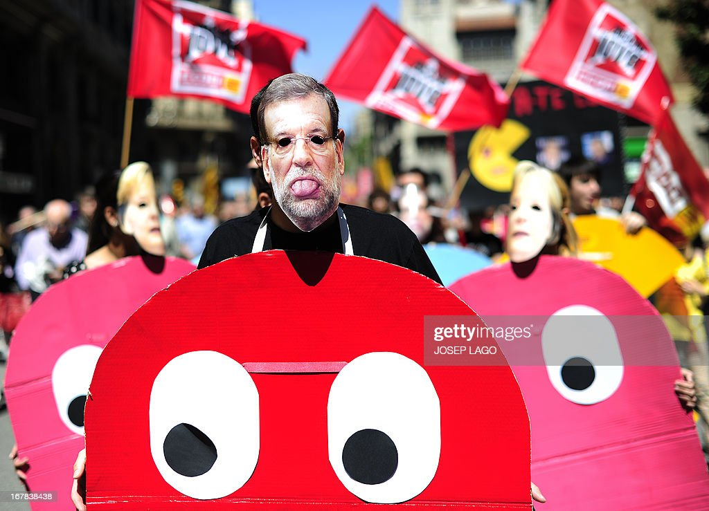 A demonstrator dressed up as a character of the video game Pac-Man and wearing a mask of Spanish Prime Minister Mariano Rajoy, takes part a Labour Day march against the Spanish government's austerity policies in the centre of Barcelona on May 1, 2013. Tens of thousands protested across the globe for May Day to press for workers' rights amid tough economic times and to back an array of other causes. AFP PHOTO / JOSEP LAGO
