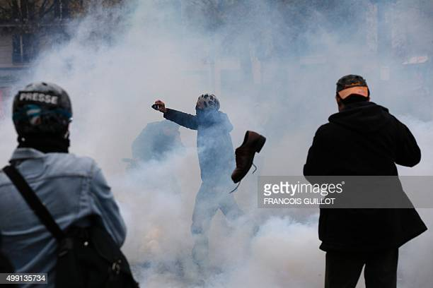 A demonstrator films as protestors clash with riot police during a rally against global warming on November 29 2015 in Paris a day ahead of the start...