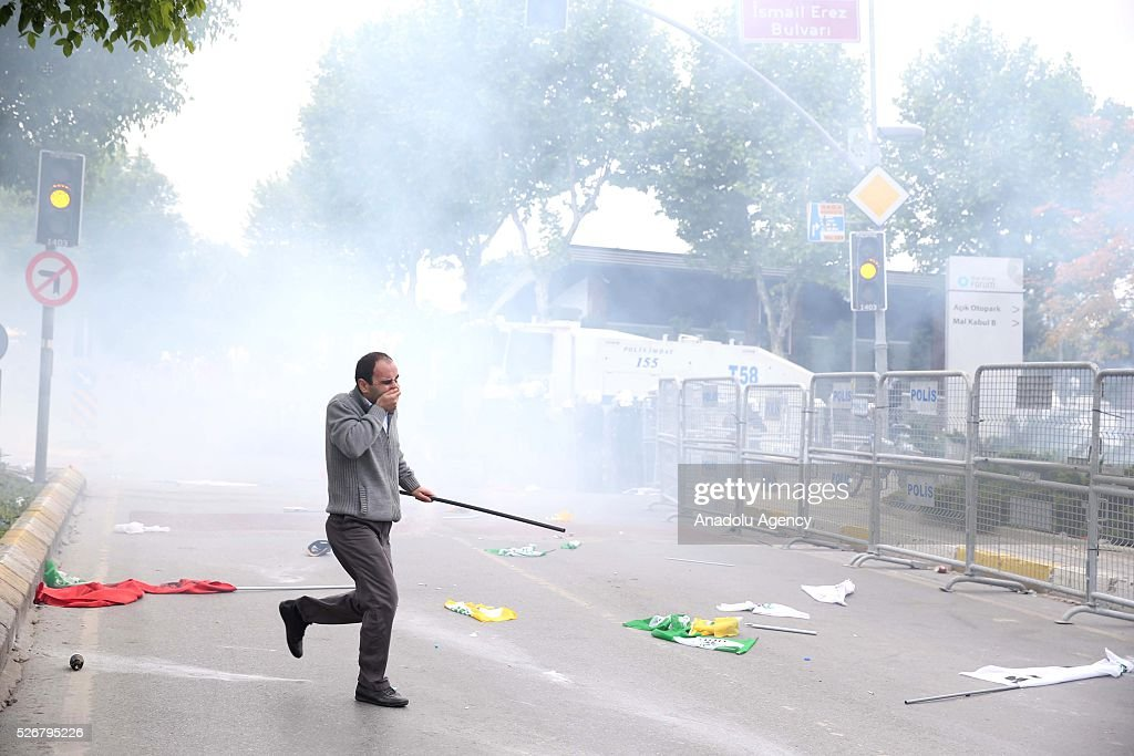 A demonstrator from a group, rejecting police's security check and carrying illegal materials, flees from riot police's intervention as they try to enter the open market area in the Bakirkoy neighborhood, where main May Day celebrations take part on May 01, 2016 in Istanbul, Turkey. Every year May Day is observed and commemorated as an official holiday all around Turkey.