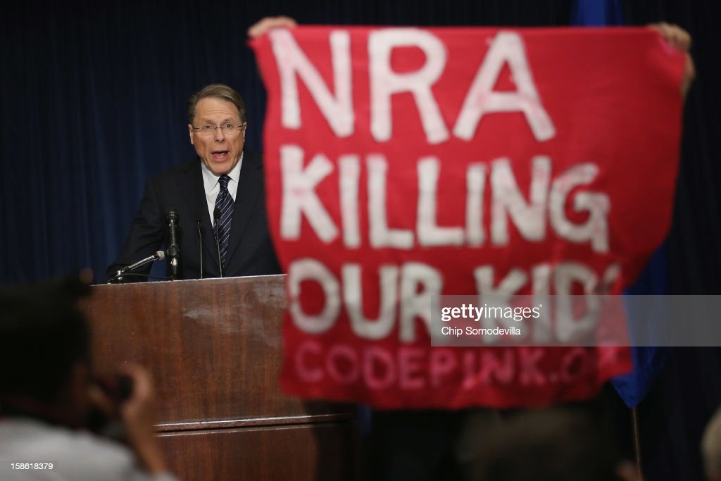 A demonstrator from CodePink holds up a banner as National Rifle Association Executive Vice President Wayne LaPierre delivers remarks during a news...