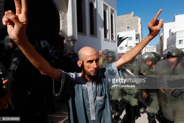 TOPSHOT A demonstrator gestures in front of Moroccan security forces during a march in defiance of a government ban in the northern Moroccan city of...