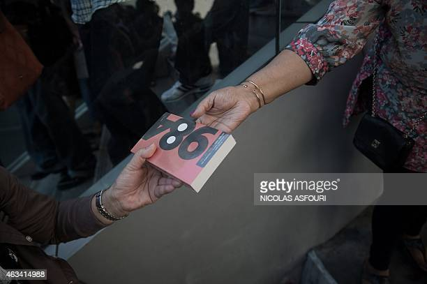 A demonstrator gives George Orwell's book '1984' to a woman outside the Art and Cultural centre during a rally in Bangkok on February 14 2015 Dozens...