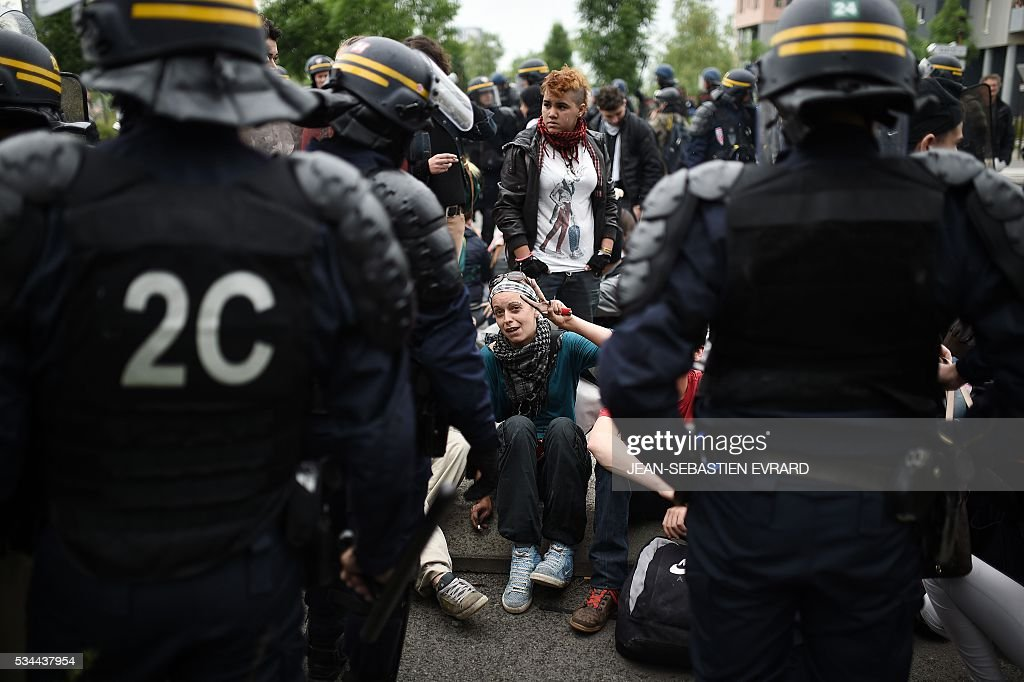 A demonstrator gives the peace sign on May 26, 2016 in Nantes, western France, during a protest against government planned labour law reforms. The French government's labour market proposals, which are designed to make it easier for companies to hire and fire, have sparked a series of nationwide protests and strikes over the past three months. Masked youths clashed with police and striking workers blockaded refineries and nuclear power stations on May 26 as an escalating wave of industrial action against labour reforms rocked France. / AFP / JEAN