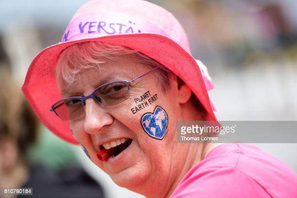 A demonstrator has painted on her face 'Planet Earth First' as she gathers with others for 'Grenzenlose Solidaritaet statt G20' during a protesters...