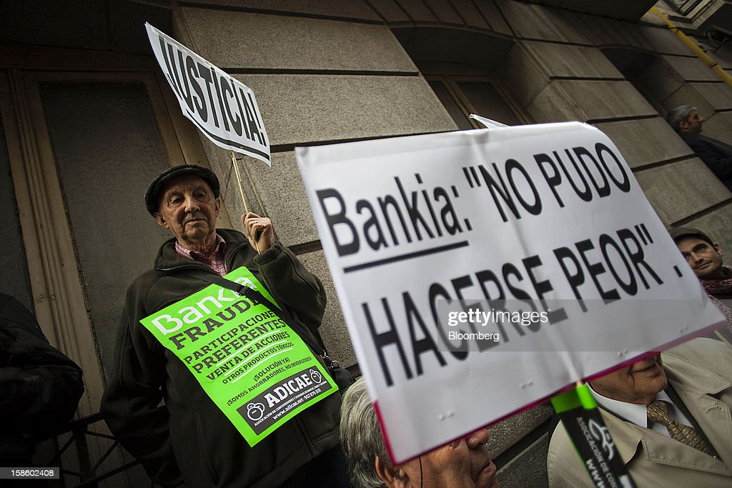 Demonstrator hold signs during a protest against Rodrigo Rato, former managing director of the International Monetary Fund and ex-chairman of Bankia Group, as he testifies at Spain's national court in Madrid, Spain, on Thursday, Dec. 20, 2012. Rato who led the seven-way savings bank merger in 2010 that formed Bankia, has appeared before lawmakers probing how the lender that was nationalized after seeking 23.5 billion euros ($28.5 billion) of state aid helped trigger a new stage of Europe's debt crisis. Photographer: Angel Navarrete/Bloomberg via Getty Images