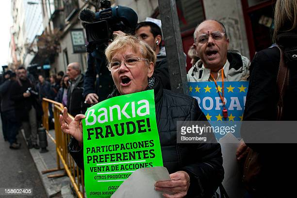 Demonstrator hold signs while chanting during a protest against Rodrigo Rato former managing director of the International Monetary Fund and...
