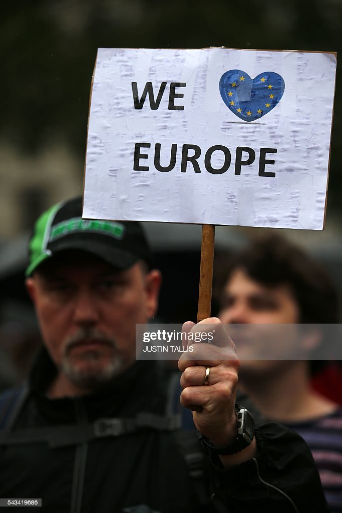 A demonstrator hold up a pro-Europe placard at an anti-Brexit protest in Trafalgar Square in central London on June 28, 2016. EU leaders attempted to rescue the European project and Prime Minister David Cameron sought to calm fears over Britain's vote to leave the bloc as ratings agencies downgraded the country. Britain has been pitched into uncertainty by the June 23 referendum result, with Cameron announcing his resignation, the economy facing a string of shocks and Scotland making a fresh threat to break away. / AFP / JUSTIN