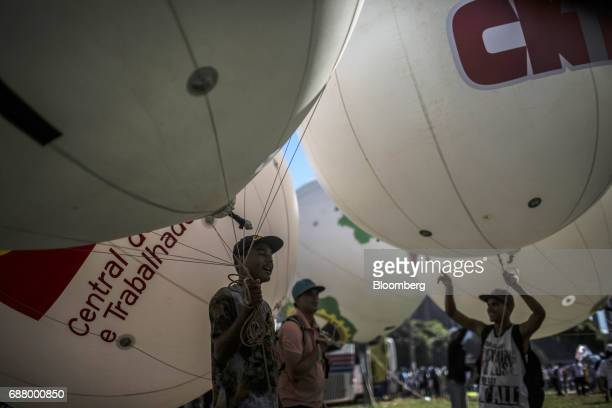 A demonstrator holds a balloon during protests outside of the National Congress demanding the resignation of President Michel Temer in Brasilia...