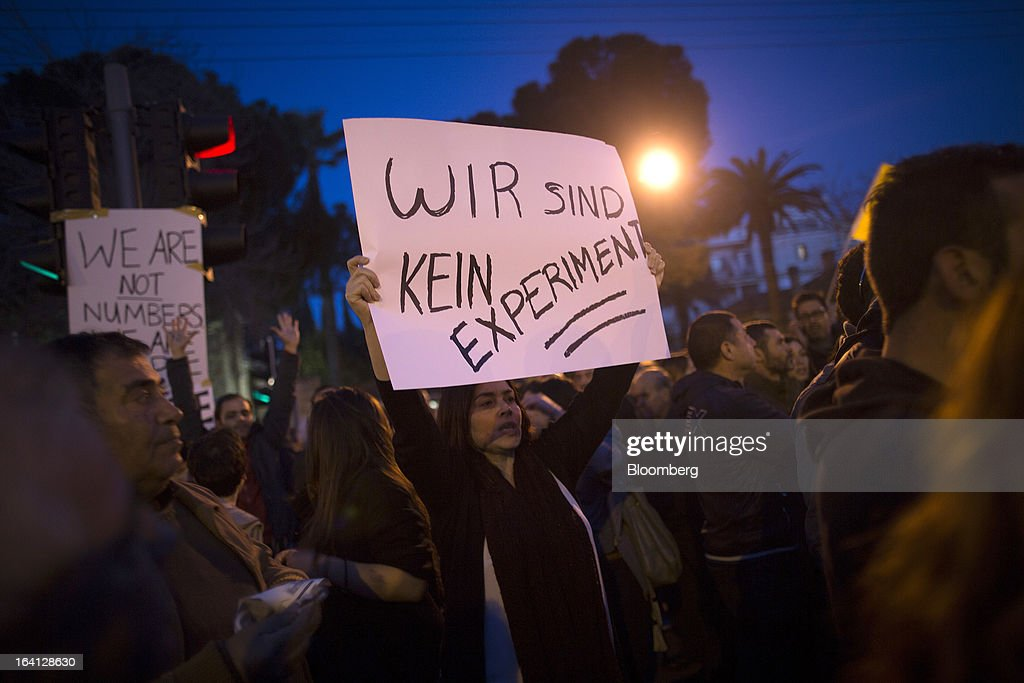 A demonstrator holds a banner in German reading 'We are not an experiment' during a protest outside the parliament against bank deposit tax plans in Nicosia, Cyprus, on Tuesday, March 19, 2013. Euro-area finance ministers told Cyprus to raise 5.8 billion euros ($7.5 billion) from bank depositors to unlock emergency loans, maintaining the revenue target while suggesting sparing small-scale savers. Photographer: Simon Dawson/Bloomberg via Getty Images