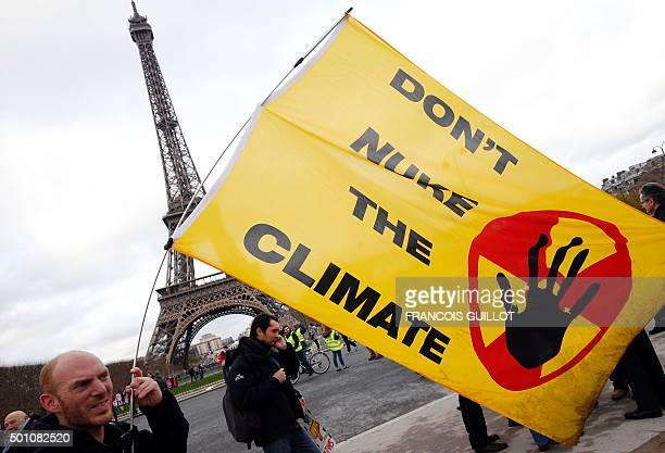 A demonstrator holds a banner reading 'Don't nuke the climate' during a rally called by several Non Governmental Organisations to form a human chain...