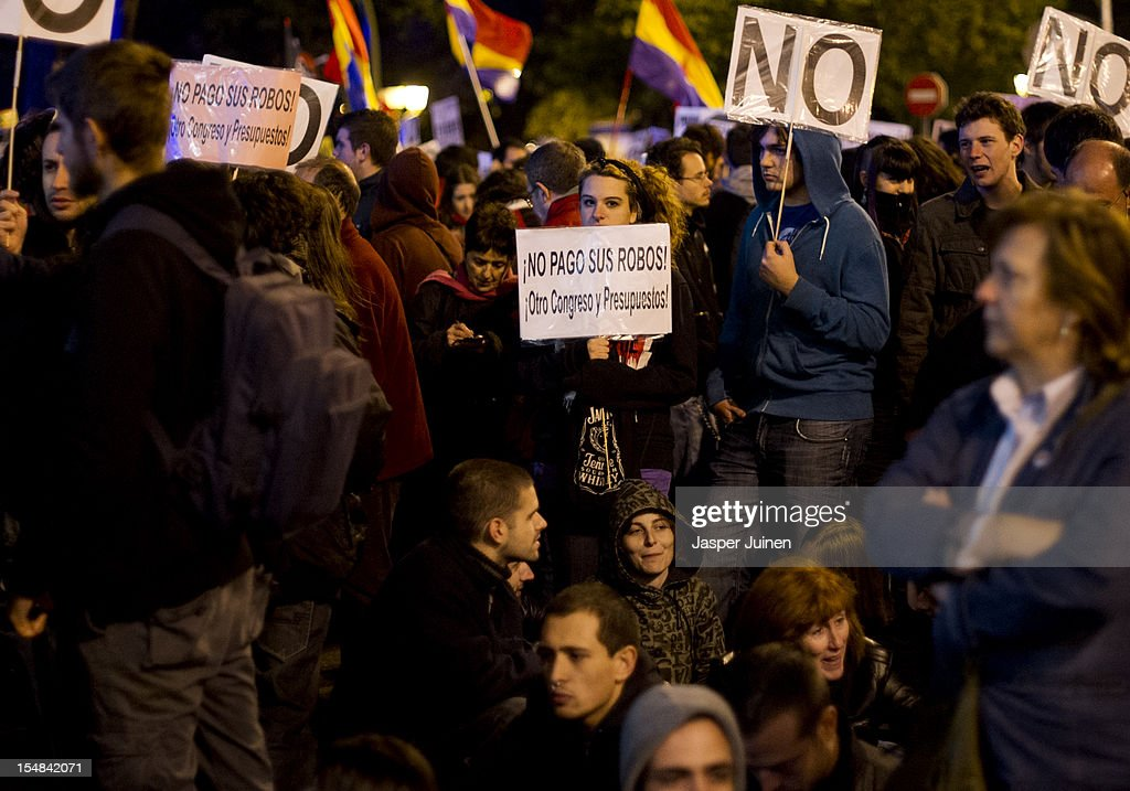 A demonstrator holds a banner reading 'I am not paying their robberies, another congress and budgets' during a protest against spending cuts and the government of Mariano Rajoy on October 27, 2012 in Madrid, Spain. Demonstrators are protesting near the Spanish Parliament against the government's austerity measures. With the economic crisis tightening it's grip, Spain is in its second recession in three years, Rajoy's governement is presssured more and more to seek aid that can easy their debts.