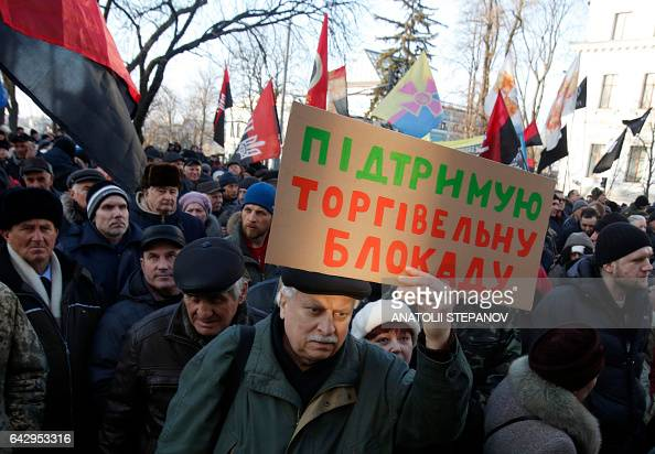 A demonstrator holds a banner reading 'keep trade blockade' as protesters attend a rally against trade with the occupied territories in Kiev on...