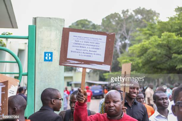 A demonstrator holds a banner reading 'No to impunity for economic crimes' on June 22 2017 in Cotonou during a protest against bad governance / AFP...