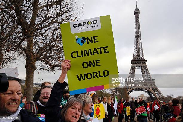 A demonstrator holds a banner reading 'One climate one world' during a rally held by several Non Governmental Organisations to form a human chain on...
