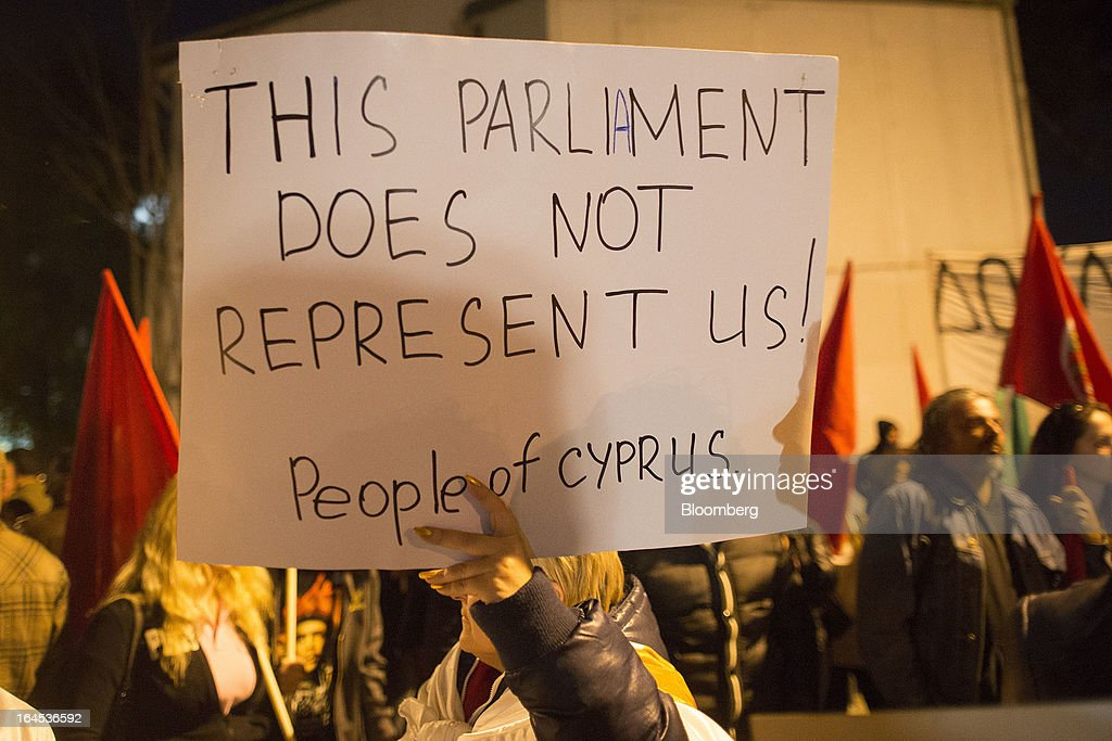 A demonstrator holds a banner reading 'this parliament does not represent us' during a protest outside the European Union House in Nicosia, Cyprus, on Sunday, March 24, 2013. Cyprus's fate hangs in the balance as euro-area finance ministers meet today to decide whether the tiny Mediterranean island has done enough for a bailout that will avert its financial collapse. Photographer: Simon Dawson/Bloomberg via Getty Images