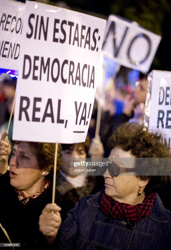 A demonstrator holds a banner reading 'Without fraud: Real democracy now!' during a protest against spending cuts and the government of Mariano Rajoy on October 27, 2012 in Madrid, Spain. Demonstrators are protesting near the Spanish Parliament against the government's austerity measures. With the economic crisis tightening it's grip, Spain is in its second recession in three years, Rajoy's governement is presssured more and more to seek aid that can easy their debts.