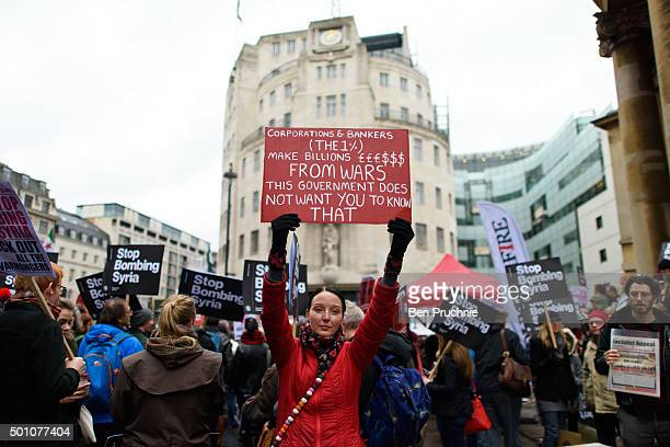 A demonstrator holds a banner with the slogan 'Corporate bankers make millions from wars this government does not want you to know that' during a...