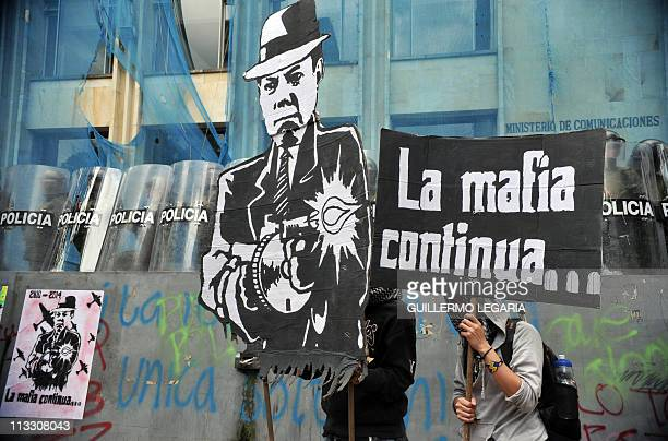 A demonstrator holds a banners depicting Colombia's President Juan Manuel Santos as a gangster during a May Day demo in Bogota Colombia on May 1 2011...
