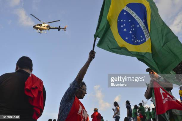 A demonstrator holds a Brazilian flag as a police helicopter flies past during protests outside of the National Congress demanding the resignation of...