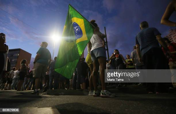 A demonstrator holds a Brazilian flag during a protest against proposed federal government reforms on March 15 2017 in Rio de Janeiro Brazil...