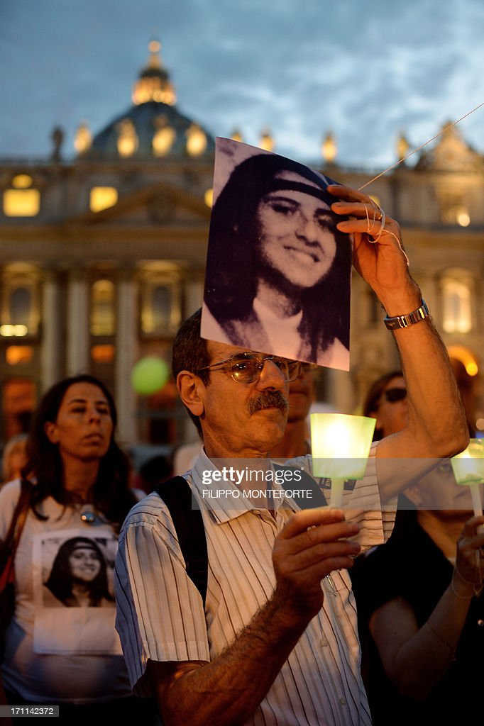A demonstrator holds a candel during a commemoration of the 30th anniversary of Emanuela Orlandi disappearance in St Peter's Square at the Vatican on June 22 2013. Fifteen-year-old Emanuela Orlandi, the daughter of a Vatican messenger who lived with his family in Vatican City, disappeared on June 22, 1983 when she went to a music lesson. The still unsolved Orlandi saw over the years a number of theories regarding the motives for the crime from claimes that the kidnapping was done by extremist Muslim terrorists to demand the release of Mehmet Ali Agca from prison after he shot pope John Paul II to latest exorcist Gabriele Amorth claiming that she was kidnapped by a member of the Vatican police for sex parties, and then murdered. AFP PHOTO/ Filippo MONTEFORTE